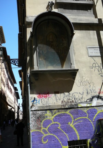 Madonna in tabernacle looks down on scrawled walls