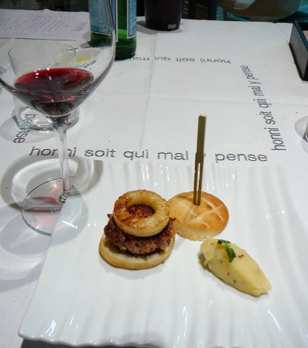 Three-bite hamburger with apple garnish and finger of mashed potato