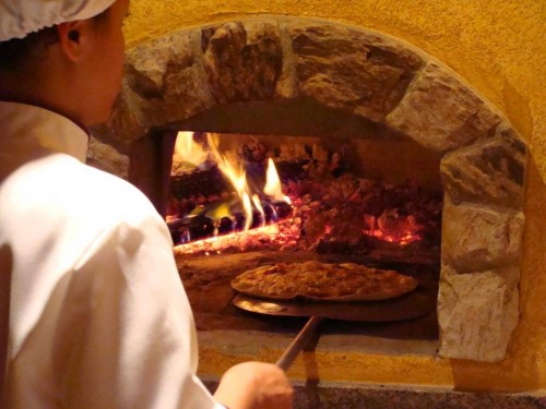 The pizzaiolo slides a pizza into the wood-burning oven